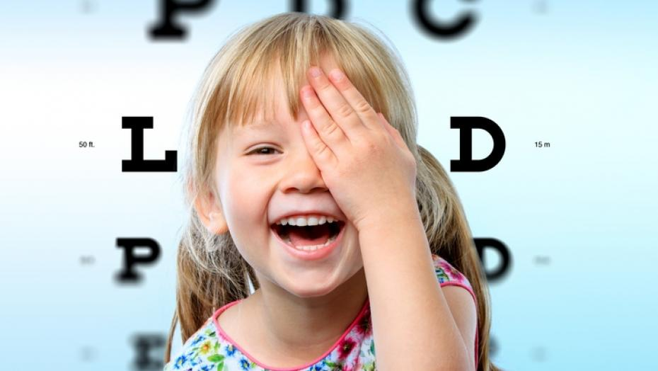 Young female smiling and using her hand to cover her left eye, she is in front of a background that resembles a Snellen eye chart